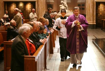 Since communion rails were removed from most Catholic churches, members of the congregation kneel in the front pew to receive the Eucharist. Rich Saal/The State Journal-Register