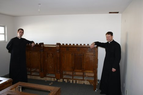 Fr. James Fryar FSSP and Fr. Justin Nolan FSSP flank a part of the new sacristycredens which will be custom fit to the sacristy room.